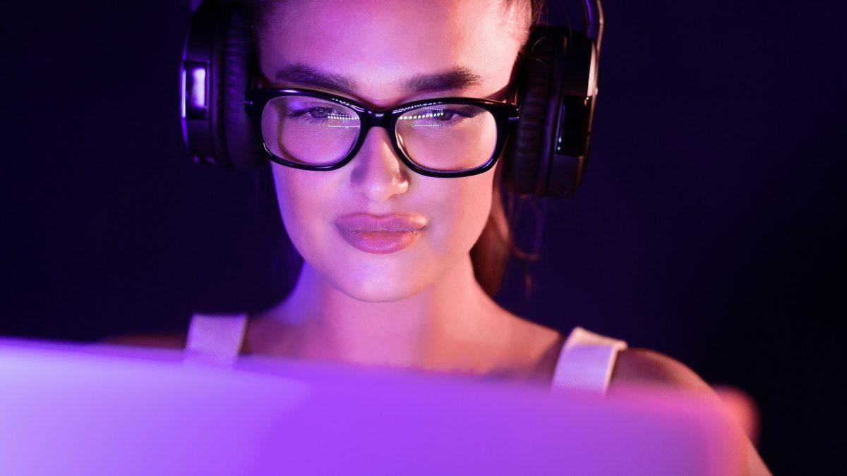 Student watching online tutorials, wearing headphones in the night